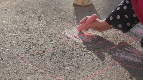 Little girl drawing on the ground