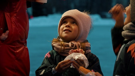 Little girl eating a donut on an ice rink