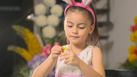 Little girl eating an easter egg with chocolate