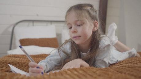 Little girl enjoys drawing hobby on bed