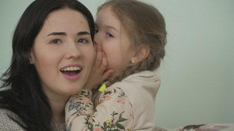 Little girl gossips in mom's ear