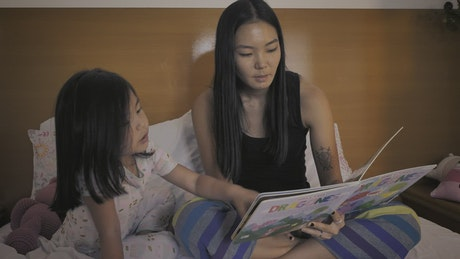 Little girl happily shows her mom a book before going to sleep