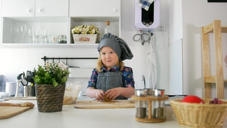 Little girl in a kitchen making cookies with dough