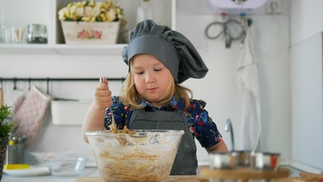 Little girl in a kitchen stirring a cookie mix