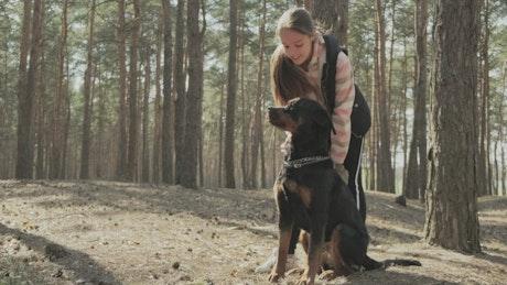Little girl kisses her dog in the park