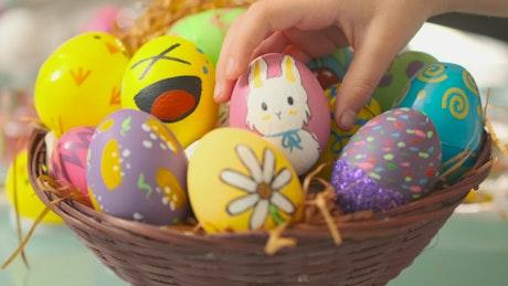 Little girl leaving an easter egg in a basket