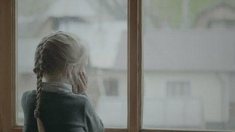 Little girl looking outside the window