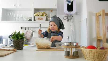 Little girl making cookie mixture in the kitchen