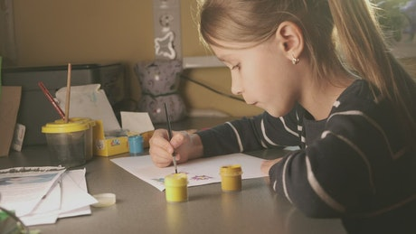 Little girl painting at a desk