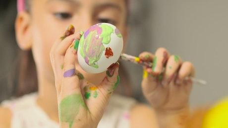 Little girl painting easter eggs, shallow focus