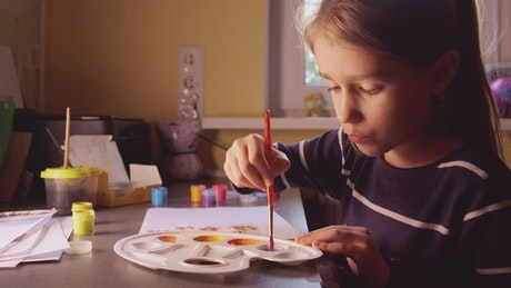 Little girl painting with watercolors at home