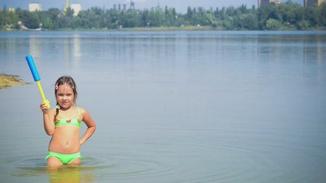 Little girl playing in a lake