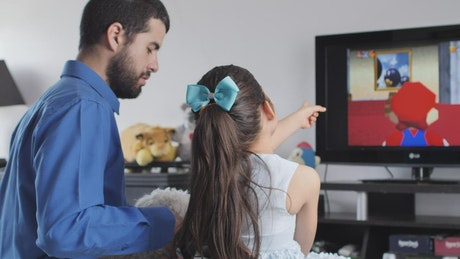 Little girl playing video games with her father