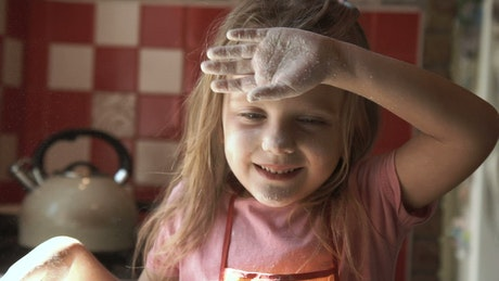 Little girl playing with flour on the kitchen