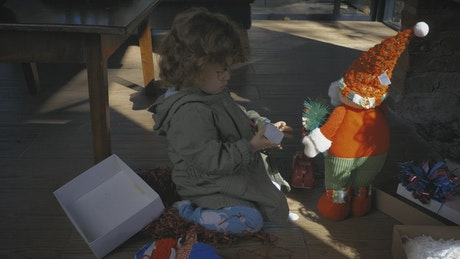 Little girl playing with gifts on Christmas morning