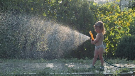 Little girl playing with the water hose