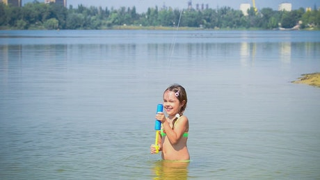 Little girl playing with toy in a lake