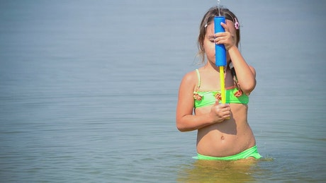 Little girl playing with water in the sea