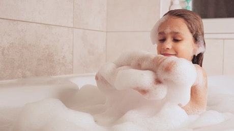 Little girl plays while taking a bath