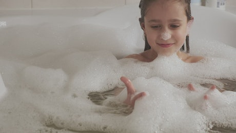 Little girl plays with foam in the bathtub