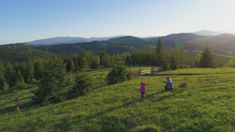 Little girl plays with her mother in the meadow
