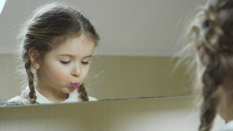 Little girl puts on lipstick in the mirror