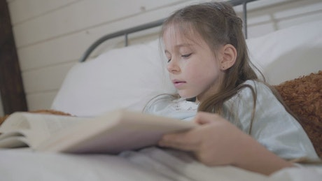 Little girl reads a story in a book