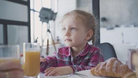 Little girl refuses orange juice for breakfast