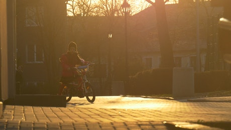 Little girl riding a bike in the sunset