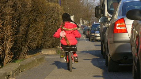 Little girl riding a bike through the streets