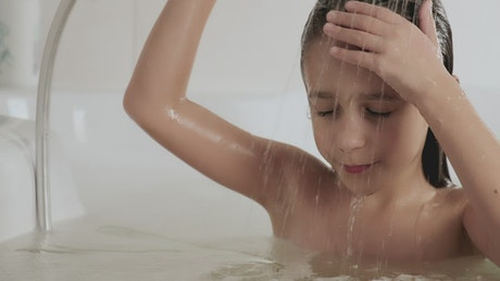 Little girl rinsing out the shampoo from her hair in the tub