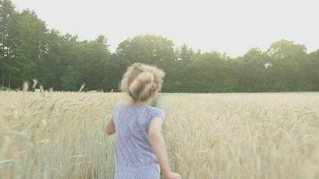 Little girl running through a wheat field