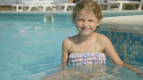 Little girl sitting in pool and smiling