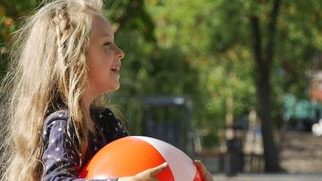 Little girl smiling holding plastic ball