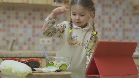 Little girl stirs salad with spoon while watching video in kitchen