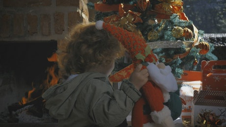 Little girl taking a gift from the Christmas tree