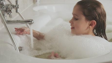 Little girl taking a sparkling bath