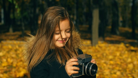 Little girl taking photos with a camera