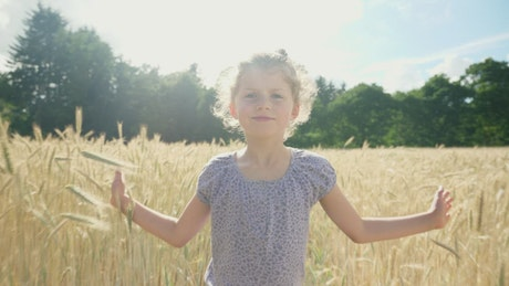 Little girl walking in the field during the summer