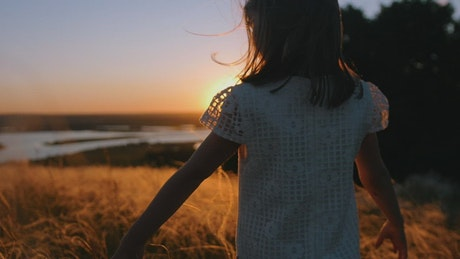 Little girl walking in the valley at sunset