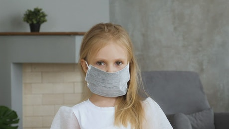 Little girl wearing a face mask at home