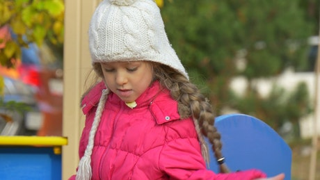 Little girl with a winter hat on the playground