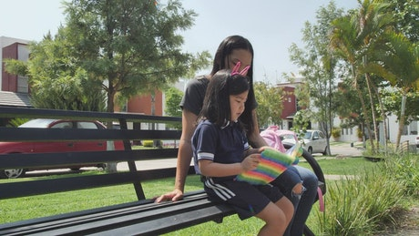 Little girl with her mom reading together in a park