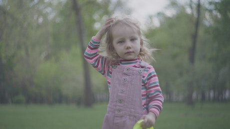 Little girl with oversized crown plays in park