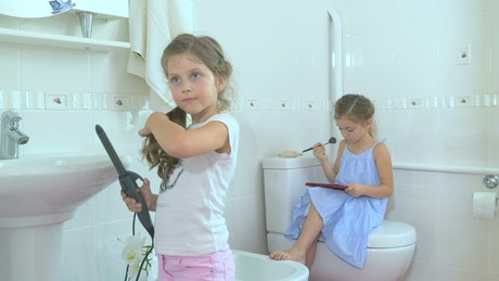 Little girls doing makeup in bathroom