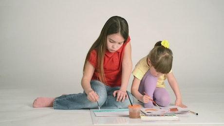 Little girls painting on the floor