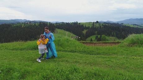 Little girls using raincoat on the meadow