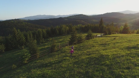 Little sisters playing in the meadow of a ranch