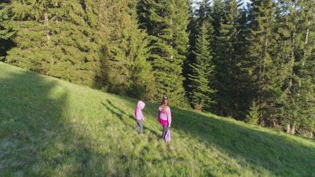 Little sisters walking down a hill in a meadow
