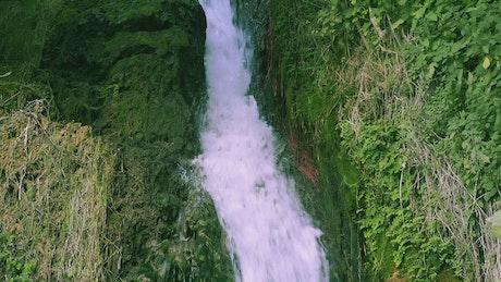 Little waterfall on green rocks